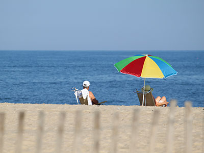 Guests of Harrison Hall Hotel in Ocean City Maryland relax on the beach.