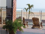 A large porch with rocking chairs looking down on the boardwalk and beach.