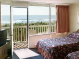 Balcony rooms with chairs overlook the end of the boardwalk and beach.