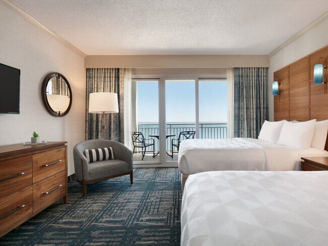 Two queen bed suite with ocean beach and pool view from balcony