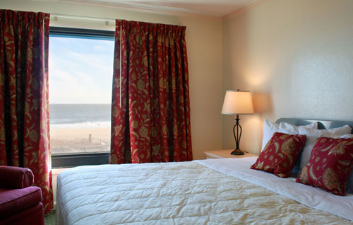 A comfortable and warm bedroom overlooking the ocean in unit 1003