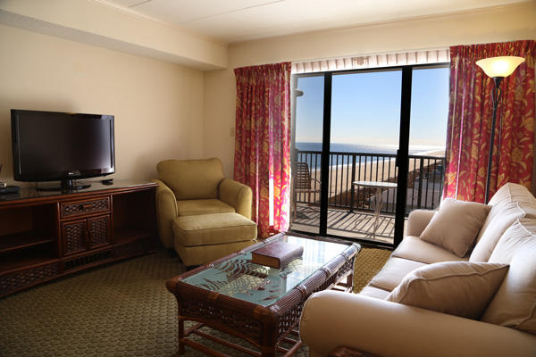 The condo balcony overlooks the beach.