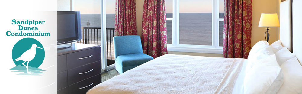 Sandpiper Dunes Condos logo with image of king bed accommodations and Atlantic Ocean view from guestroom